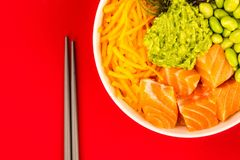 Hawaiian Style Raw Salmon Sashimi Poke Bowl With Edamame Beans A. Nd Seaweed Against A Red Background Stock Images