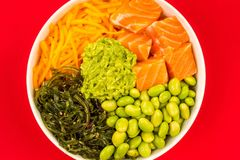 Hawaiian Style Raw Salmon Sashimi Poke Bowl With Edamame Beans A. Nd Seaweed Against A Red Background Royalty Free Stock Image