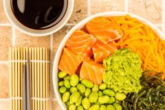 Hawaiian Style Raw Salmon Sashimi Poke Bowl With Edamame Beans A. Nd Seaweed On A Tiled Kitchen Table Top Stock Photos