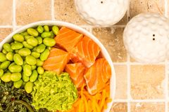 Hawaiian Style Raw Salmon Sashimi Poke Bowl With Edamame Beans A. Nd Seaweed On A Tiled Kitchen Table Top Stock Photo