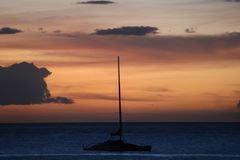 Hawaiian sunset. With catamaran silhouetted in evening light Royalty Free Stock Image
