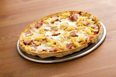 Hawaiian Thin Crust Pizza. Pizza texture with olives on wood table Royalty Free Stock Images