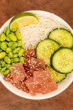 Hawaiian Tuna Fish Poke bowl With Noodles and Edamame Beans. Against A Red Background Royalty Free Stock Photos