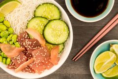 Hawaiian Tuna Fish Poke bowl With Noodles and Edamame Beans. On A Dark Wooden Kitchen Table Background Royalty Free Stock Images