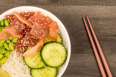 Hawaiian Tuna Fish Poke bowl With Noodles and Edamame Beans. On A Dark Wooden Kitchen Table Background Stock Images