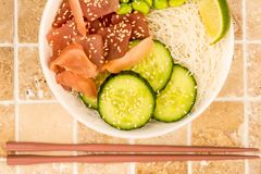 Hawaiian Tuna Fish Poke bowl With Noodles and Edamame Beans. On A Tiled Kitchen Table Top Royalty Free Stock Photography