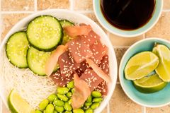 Hawaiian Tuna Fish Poke bowl With Noodles and Edamame Beans. On A Tiled Kitchen Table Top Royalty Free Stock Photos