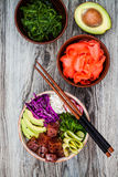 Hawaiian tuna poke bowl with seaweed, avocado, red cabbage, radishes and black sesame seeds. Hawaiian tuna poke bowl with seaweed, avocado, red cabbage Stock Photos