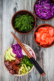 Hawaiian tuna poke bowl with seaweed, avocado, red cabbage, radishes and black sesame seeds.