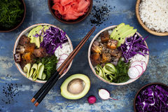 Hawaiian tuna poke bowl with seaweed, avocado, red cabbage slaw, radishes and black sesame seeds. Top view, overhead, flat lay Royalty Free Stock Photo