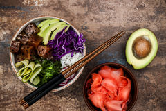 Hawaiian tuna poke bowl with seaweed, avocado, red cabbage slaw, radishes and black sesame seeds.