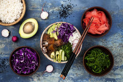 Hawaiian tuna poke bowl with seaweed, avocado, red cabbage slaw, radishes and black sesame seeds. Top view, overhead, flat lay Stock Photo