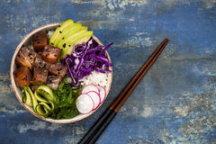 Hawaiian tuna poke bowl with seaweed, avocado, red cabbage slaw, radishes and black sesame seeds. Top view, overhead, flat lay, copy space Royalty Free Stock Photography