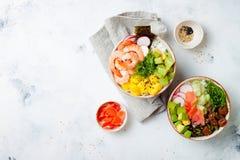 Hawaiian tuna and shrimp poke bowls with seaweed, avocado, mango, pickled ginger, sesame seeds. royalty free stock image