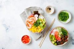 Hawaiian tuna and shrimp poke bowls with seaweed, avocado, mango, pickled ginger, sesame seeds. royalty free stock images