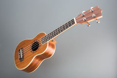Hawaiian ukulele guitar on gray background Royalty Free Stock Images