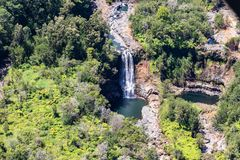 Hawaiian waterfall and pool, aerial view, near Hilo, Hawaii. Tropical rainforest surrounding banks. Aerial view of waterfall near Hilo, Hawaii. Water flows over royalty free stock photography