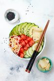Hawaiian watermelon poke bowl with avocado, cucumber, mung bean sprouts and pickled ginger. Top view, overhead