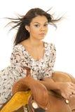 Hawaiian woman bird dress lean on saddle hair blowing Royalty Free Stock Photography