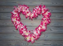 Hawaiian wreath of flowers in the shape of heart on a blue wooden background. Day of lovers. Denis the saint valentine, love stock photo