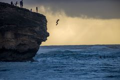 Hawaiin girl jumping off a cliff into the pacific ocean. Little girl cliff jumping on the island of Kauai, Hawaii, USA Stock Photo