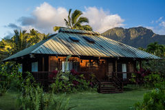 Hawaiin native home with mountains in the background. A traditional looking Hawaiin home on the island of Kauai. Mountains rise in the background Stock Photos