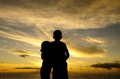 Hawaiin sunset. A brother and sister holding each other as they watch the sun setting over the Pacific Ocean on the North shore of Oahu in Hawaii Stock Images