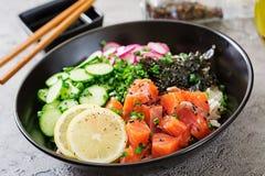 Hawaiische Lachsfische stoßen Schüssel mit Reis, Rettich, Gurke, Tomate, Samen des indischen Sesams und Meerespflanzen stockbilder