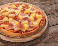 Hawaiische Pizza auf dem alten Brett Stockbild