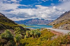 Hawea lake near town of Wanaka in New Zealand. Beatiul blue Hawea lake near town of Wanaka in New Zealand, highway picture of New Zealands mountain landscape stock images