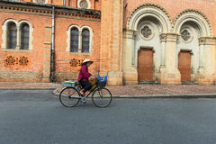 An hawker ( saleswoman ) with conical hat is driving beside Saigon Notre Dame Cathedral Royalty Free Stock Photo