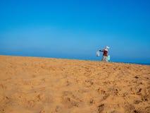 Hawker. Vietnamese Hawker Walking in Sand Dunes, Poppular Travel in Mui Ne, Vietnam on Sunny Day stock image