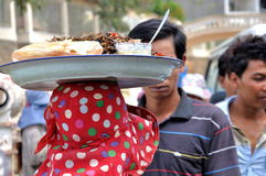 Hawking Food. A women hawking Cambodian food on her head in Cambodia royalty free stock images