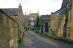 Haworth street scene, west yorkshire, England. A street behind the church in Haworth, West Yorkshire, showing cobbles and stone built houses and the church door Stock Photography