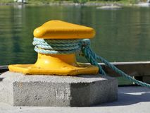 Green-blue hawser. Hawser tied on a yellow bollard Royalty Free Stock Photography