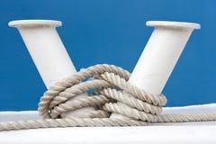 Hawser and white mooring bitt. Hawser and white bollard on board of blue boat Stock Photo