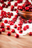 Hawthorn berries in the bowl and scattered on the table Stock Photo