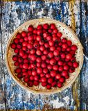 Hawthorn in a wicker bamboo bowl. Ripe hawthorn in a woven bamboo bowl on aged wooden background Stock Photo