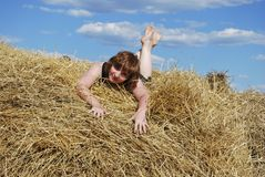 Hay. Stack  and young woman on distant plan Stock Photos