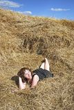 Hay. Stack and young woman on distant plan Royalty Free Stock Photography