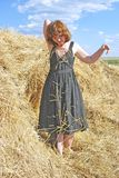 Hay. Stack and young woman on distant plan Royalty Free Stock Images