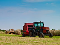 Hay Bailer and Bales. After the hay is baled then the bales must be stacked Stock Images