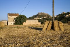 Hay bails in foreground with background of Parador de Cardona, a 9th Century medieval hillside Castle, near Barcelona, Catalonia,  Royalty Free Stock Photography