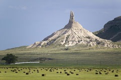 Hay bails in front of Chimney Rock National Historic Site. Nebraska, the most famous site on the Oregon Trail for early settlers and pioneers Royalty Free Stock Image