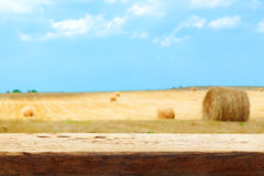 Hay bale field blur tabletop wooden background Stock Photo