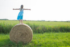 Hay bale. Happy young girl standing on a hay bale Royalty Free Stock Images