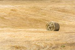 Hay bales lies singularly in the valley of a hilly and rural region stock photos