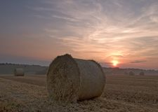 Hay bale sunset. Sunset in a freshly cut field with hay bales in the foreground Royalty Free Stock Images