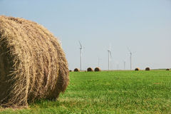 Hay Bale And Wind Turbines. Hay bale and green grass in the foreground and Kansas wind farm in the distance Stock Images