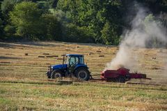 Hay baler in the field. Hay baler and hay bales in the field royalty free stock photography